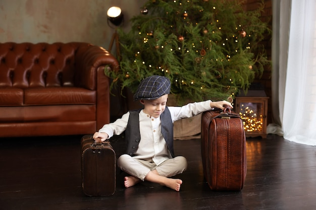 Kleine jongen zit op houten vloer in de woonkamer van kerstmis