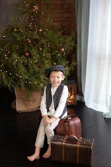 Kleine jongen zit op koffer door kerstboom