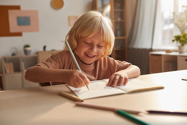 Kleine jongen zitten aan de tafel en het maken van aantekeningen in notitieblok hij zijn huiswerk thuis doet