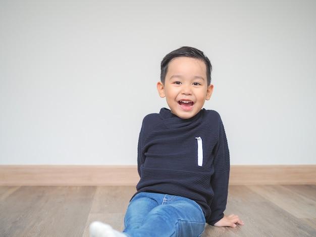 Kleine jongen zittend op de vloer met een glimlach