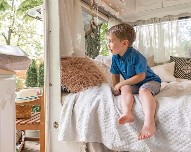 Kleine jongen zittend op een bad in een caravan