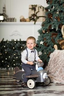 Kleine jongen zittend op een vintage speelgoed vliegtuig in de buurt van een kerstboom.