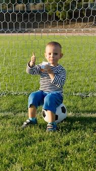 Kleine jongen zittend op een voetbal in een doelpaal met een duim omhoog teken van goedkeuring met zijn hand