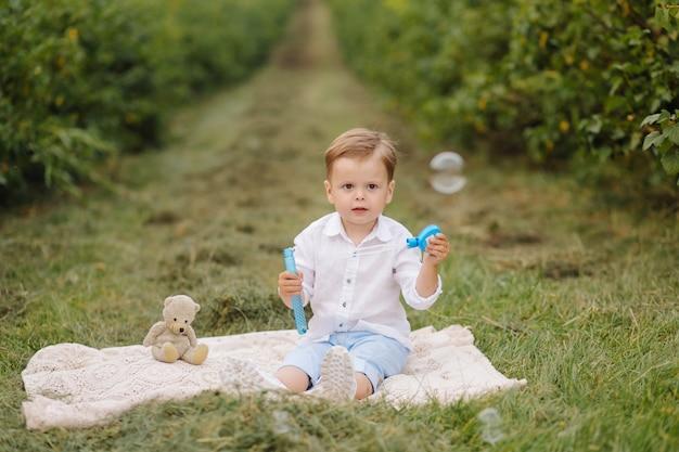 Kleine jongen zittend op picknick plaid in cottage tuin