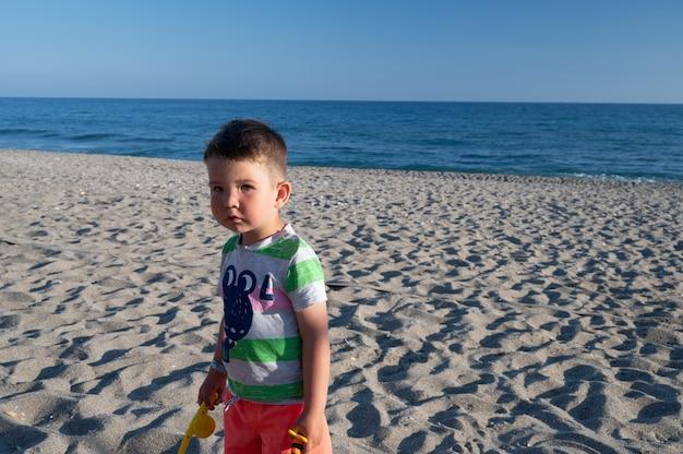 Kleine jongen zoekt zijn moeder op het strand