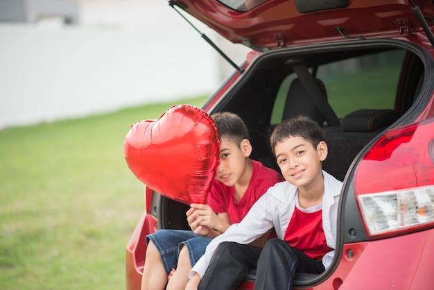 Kleine jongens die op de achterdeur van de auto zitten met in hand ballonhart