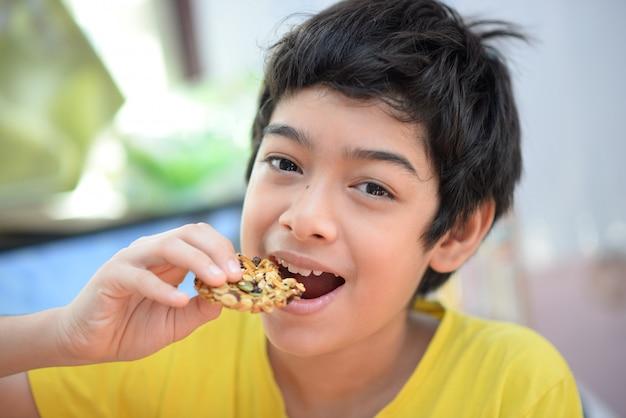 Kleine jongens die tijd van de cashewnoot de gezonde snack eten