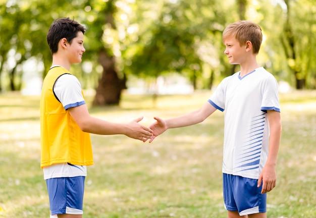 Kleine jongens handen schudden voor een voetbalwedstrijd