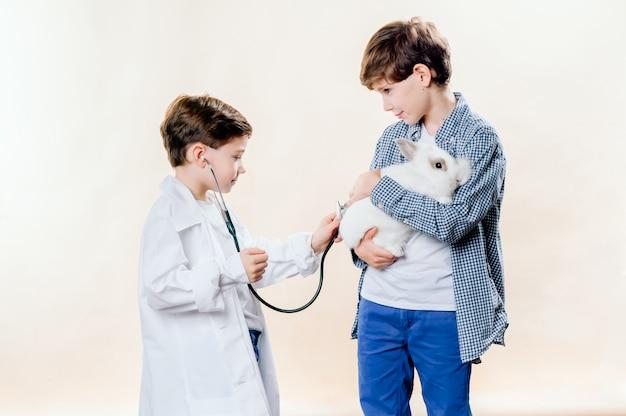 Kleine jongens spelen dierenarts met een konijn