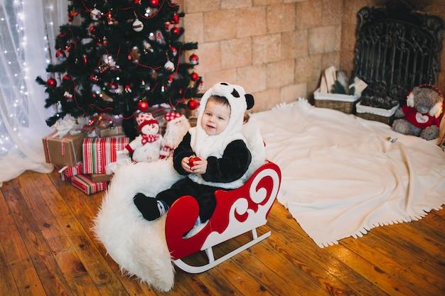 Kleine jongensbaby zat naast versierde kerstboom met geschenken en cadeautjes.
