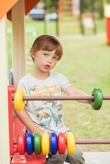 Kleine jongenskind speelt met een telraam op de speelplaats