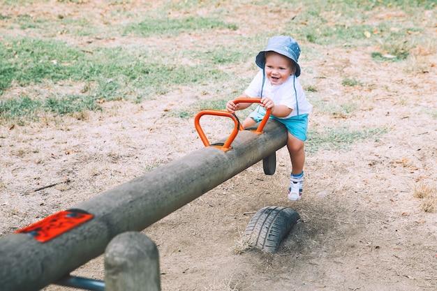 Kleine jongenskind spelen op een speelplaats gelukkige familie op speelplaats op zomerdag in een park