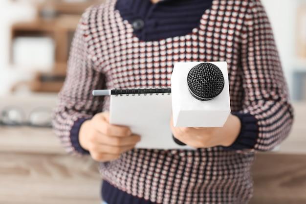 Kleine journalist met microfoon met een interview in kantoor, close-up