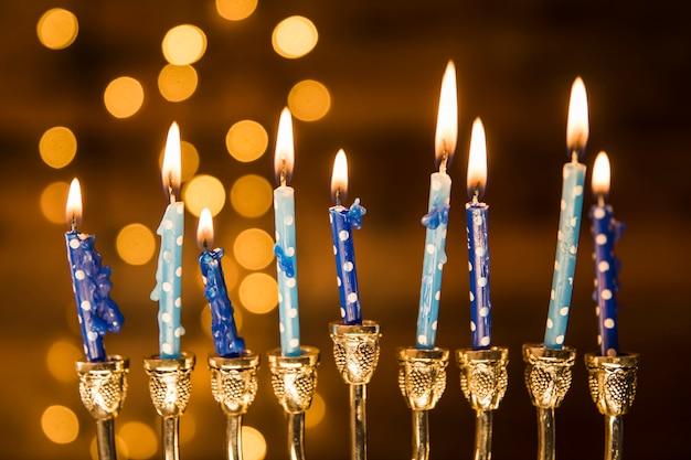 Kleine kaarsen van menorah dichtbij abstracte lichten