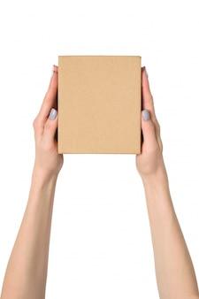 Kleine kartonnen doos in vrouwelijke handen. bovenaanzicht isoleren