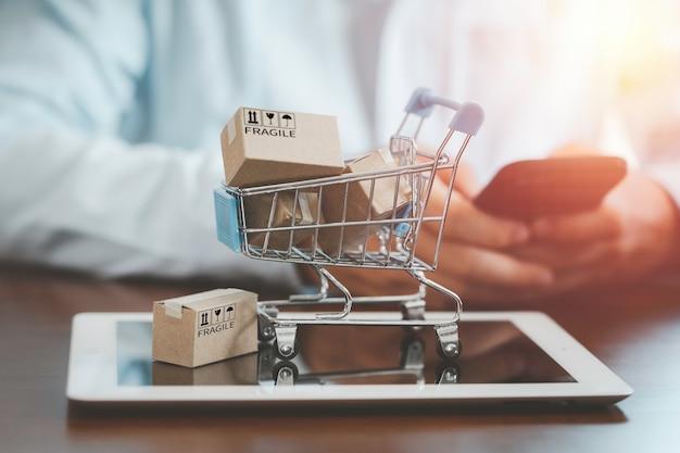 Kleine kartonnen doos met winkelwagentje op tablet en klant gebruikt smartphone om bestelling in te voeren voor online winkelconcept.