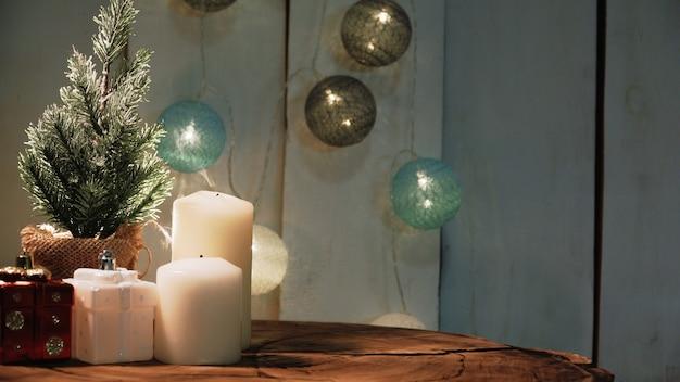 Kleine kerstboom en kaarsen op een houten oppervlak