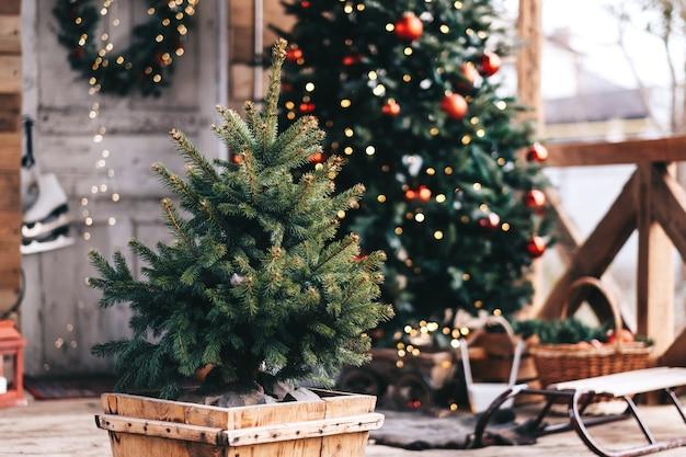 Kleine kerstboom in een houten pot in de achtertuin met kerstversiering