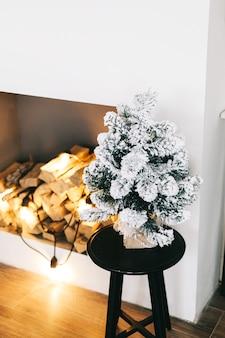 Kleine kerstboom in helder witte woonkamer op tafel.