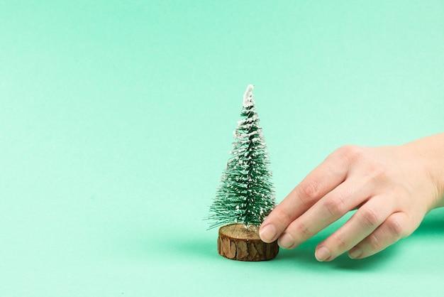 Kleine kerstboom in vrouwenhand op green