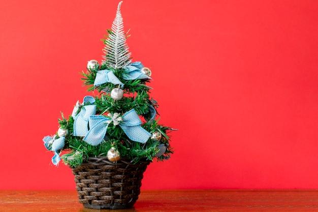 Kleine kerstboom met blauwe linten en rode achtergrond