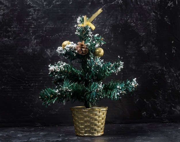Kleine kerstboom op zwarte abstracte achtergrond.
