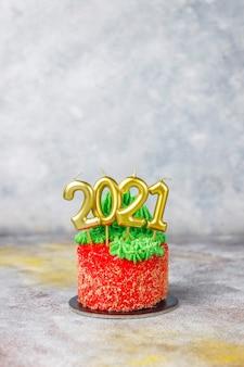 Kleine kersttaart versierd met zoete figuren van de kerstboom, de kerstman en kaarsen.