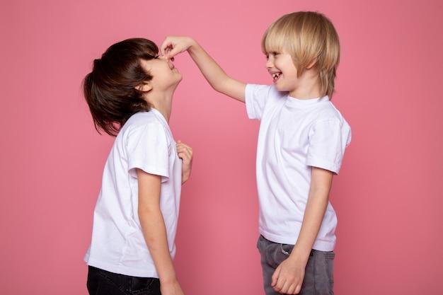 Kleine kind jongens schattige zoete spelen met elkaar op roze muur