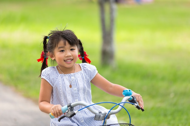Kleine kind meisje berijdende fiets in park