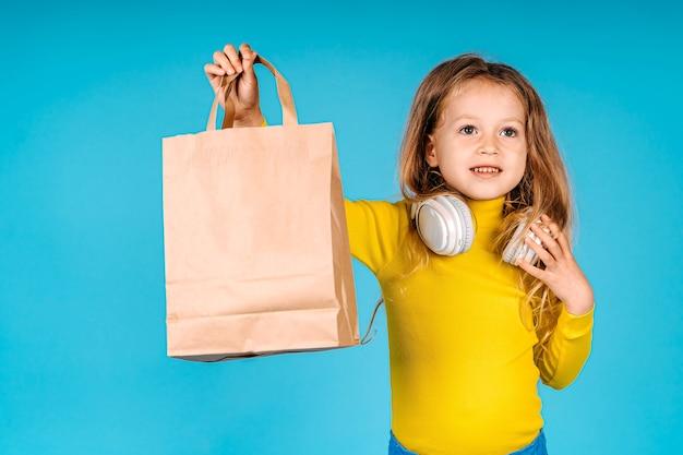 Kleine kind meisje houdt papieren zak geïsoleerd op blauwe achtergrond