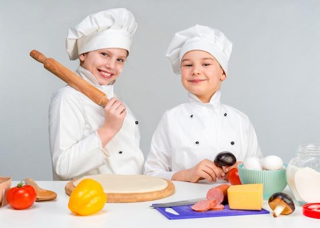 Kleine kinderen aan een tafel pizza maken