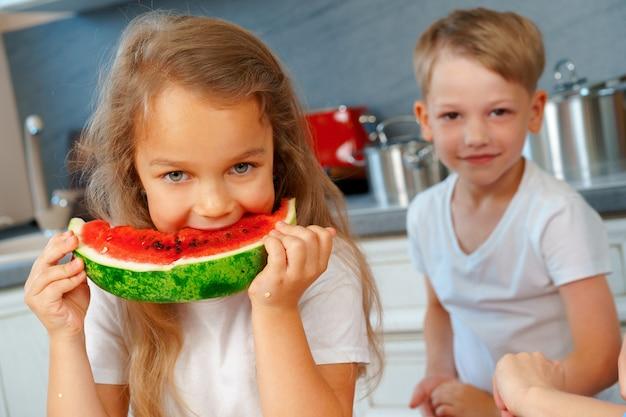 Kleine kinderen, broer en zus die watermeloen eten