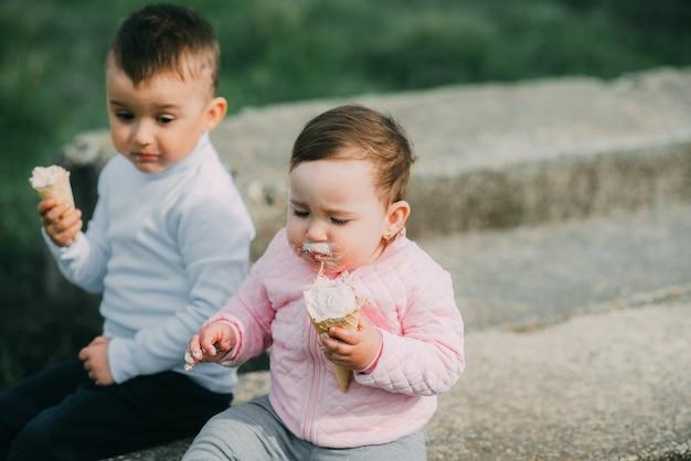 Kleine kinderen buiten in het dorp ijs eten