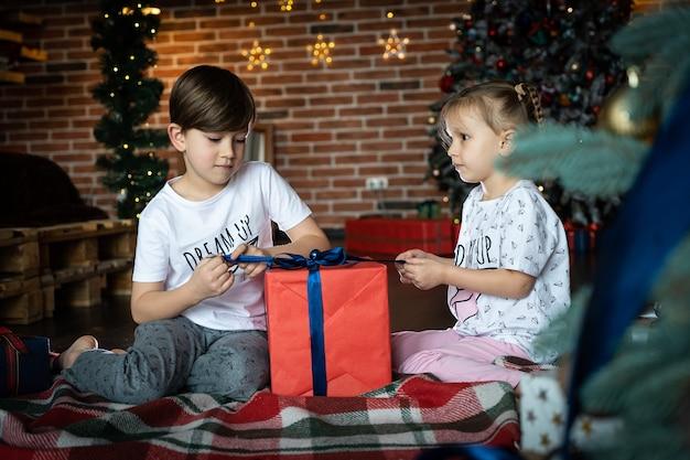 Kleine kinderen die cadeautjes openen naast de boom en de open haard in een gezellig huis om vrolijk kerstfeest te vieren