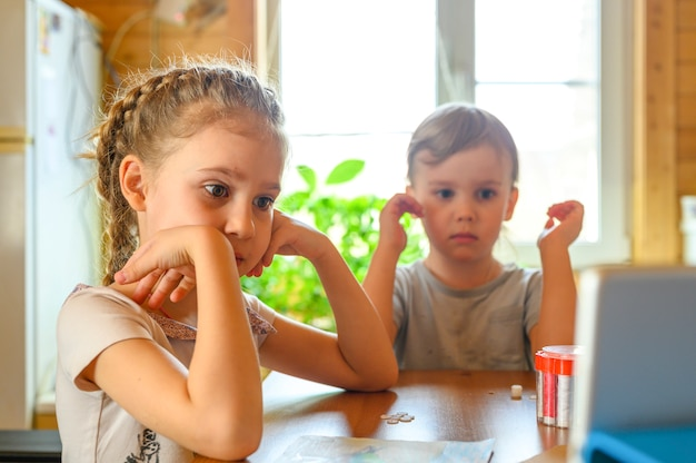 Kleine kinderen die een tablet thuis gebruiken