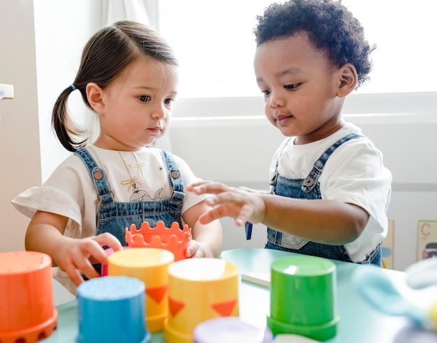 Kleine kinderen die speelgoed spelen in het leercentrum