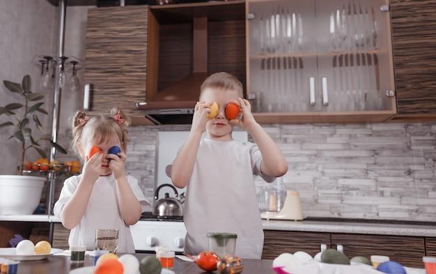 Kleine kinderen die thuis plezier hebben met beschilderde paaseieren. broer en zus, die beschilderde eieren vasthouden en grappige gezichten trekken. gelukkig pasen