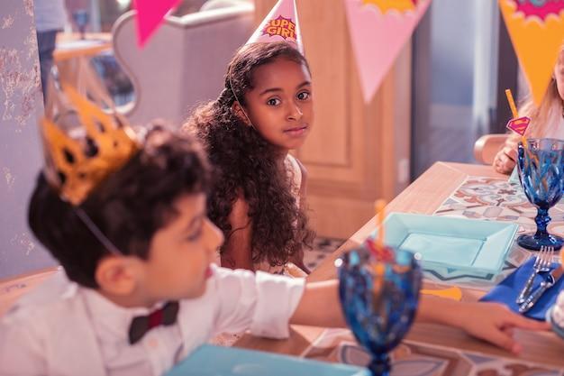 Kleine kinderen een verjaardagsfeestje bijwonen en aan tafel zitten