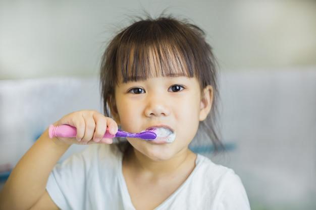 Kleine kinderen gebruiken tandenborstel om haar tanden te poetsen