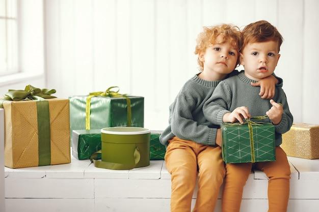 Kleine kinderen in de buurt van de kerstboom in een grijze trui