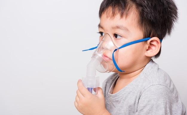 Kleine kinderen jongen met behulp van stoominhalator