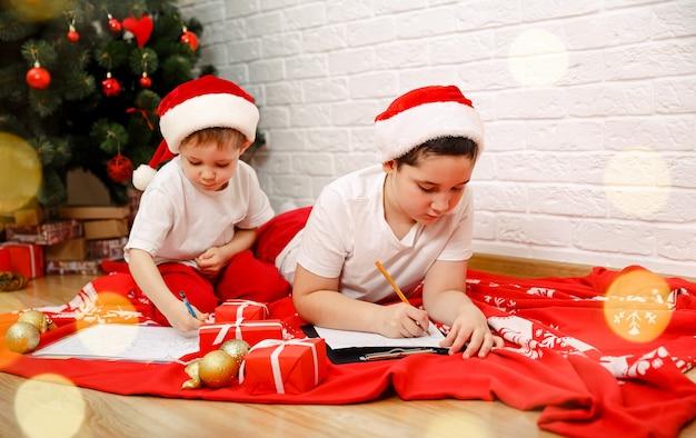 Kleine kinderen jongens schrijven de brief aan de kerstman thuis binnenshuis