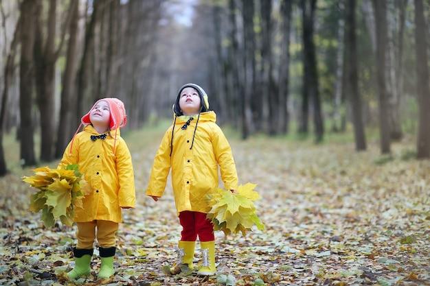 Kleine kinderen lopen in het herfstpark in de herfst van bladeren
