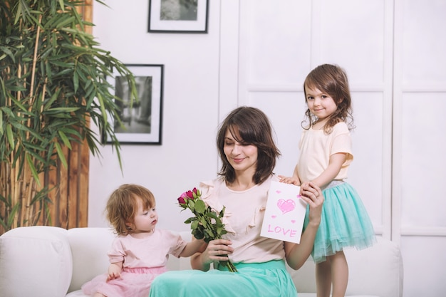 Kleine kinderen meisjes mooi en schattig geven bloemen en moeders kaart in huis voor de vakantie