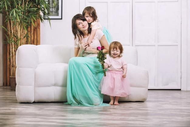 Kleine kinderen meisjes schattig mooi en geven bloemen aan de moeder in huis voor de vakantie
