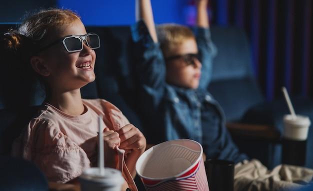 Kleine kinderen met 3d-bril en popcorn in de bioscoop kijken naar een film