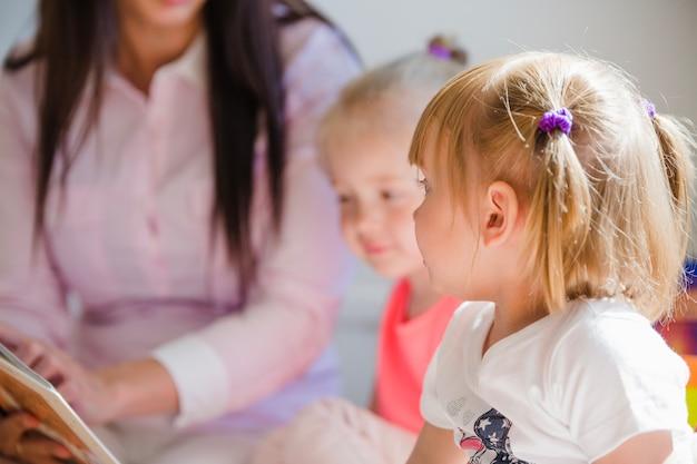 Kleine kinderen met verpleegster in kleuterschool