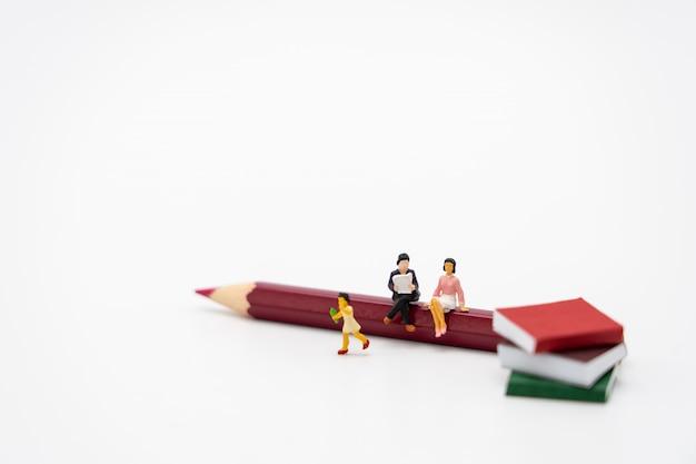 Kleine kinderen miniatuurmensen die zich op boeken bevinden