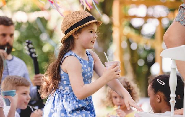 Kleine kinderen op de grond buiten in de tuin in de zomer, spelen en drinken.
