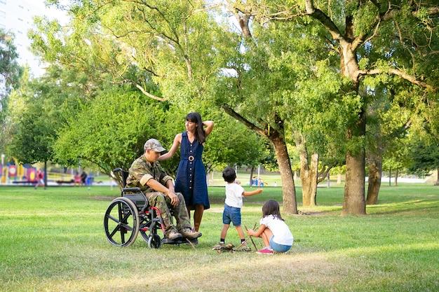 Kleine kinderen regelen brandhout voor kampvuur buiten in de buurt van moeder en gehandicapte militaire vader in rolstoel. gehandicapte veteraan of familie buitenshuis concept